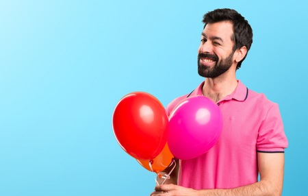 Handsome young man holding balloons and  winking on colorful background