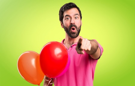 Handsome young man holding balloons and  pointing to the front on colorful background Stock Photo