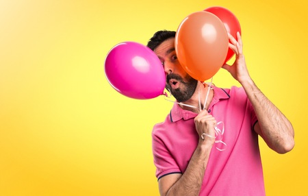 Handsome young man holding balloons on colorful background