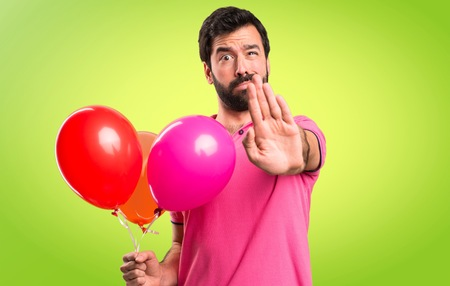 Handsome young man holding balloons and  making stop sign on colorful background