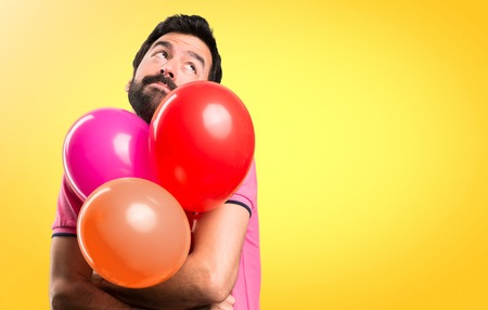 Handsome young man  making unimportant gesture and holding balloons on colorful background Stock Photo