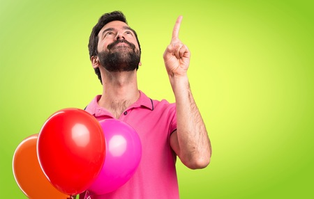 Handsome young man holding balloons and  pointing up on colorful background Stock Photo