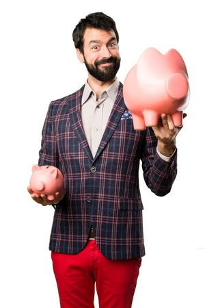 Happy Well dressed man holding a piggybank on white background