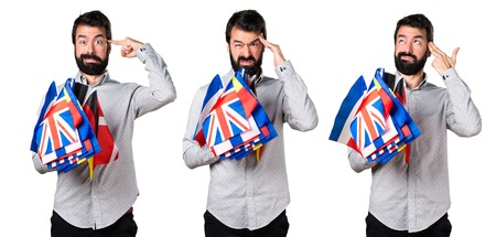 Frustrated handsome man with beard holding many flags Stock Photo