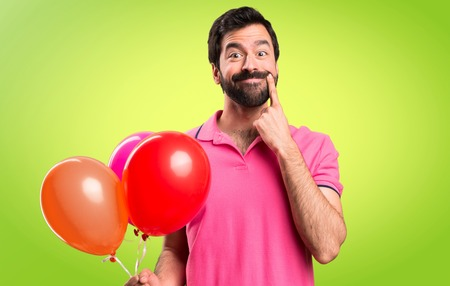 Happy handsome young man holding balloons on colorful background