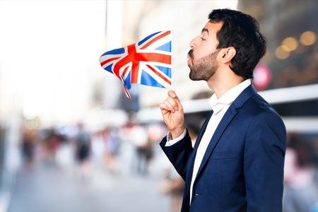 Handsome man holding an UK flag on unfocused background