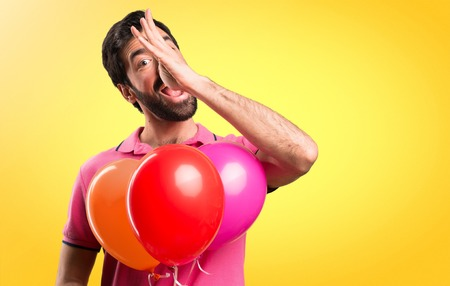 Handsome young man  making a joke holding balloons on colorful background Stock Photo