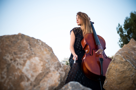 Young beautiful girl with her cello on the outside Stock Photo