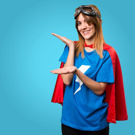 Pretty superhero girl presenting something on colorful background