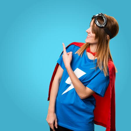 Pretty superhero girl pointing back on colorful background Reklamní fotografie
