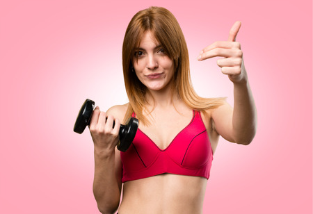 Beautiful sport woman with dumbbells doing coming gesture on colorful background