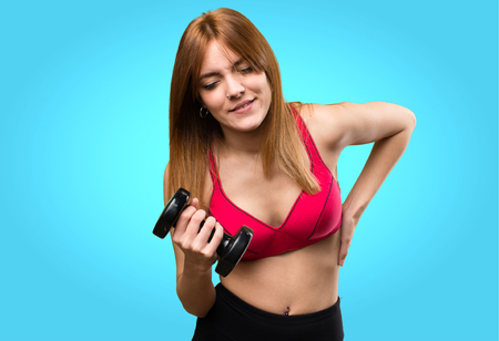 Beautiful sport woman with dumbbells with back pain on colorful background Stock Photo