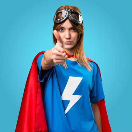 Pretty superhero girl making gun gesture on colorful background