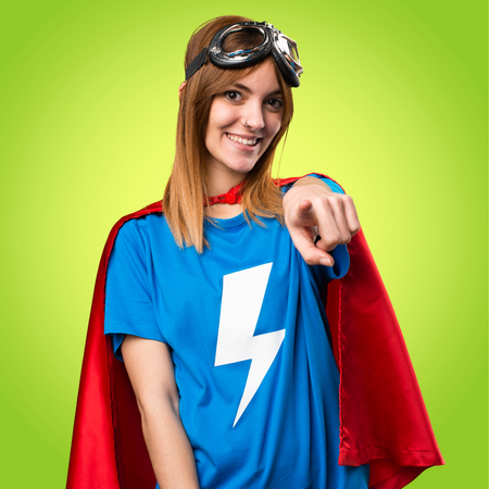 Pretty superhero girl pointing to the front on colorful background Reklamní fotografie