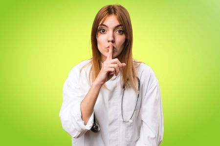Young doctor woman making silence gesture on colorful background