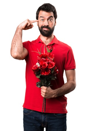 Handsome man holding flowers making crazy gesture over white background