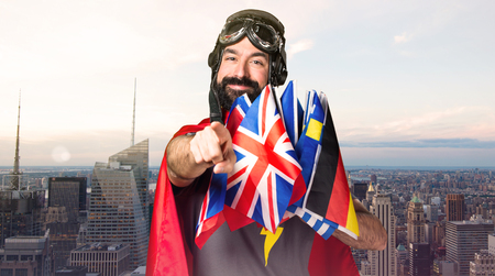 Superhero with a lot of flags pointing to the front on unfocused city background