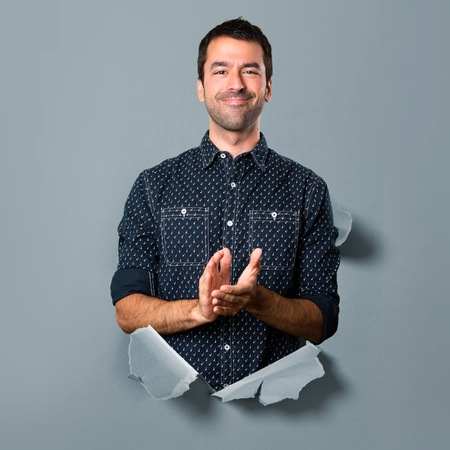 Brunette man applauding through a paper hole Stock Photo