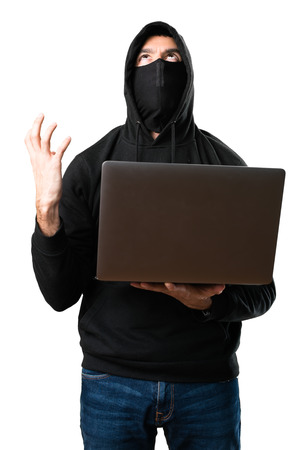 Frustrated hacker with his computer on isolated white background Stock Photo
