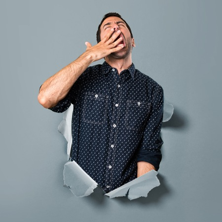 Brunette man yawning through a paper hole