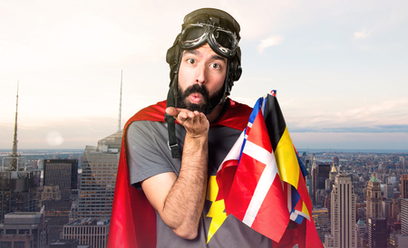 Superhero with a lot of flags sending a kiss on unfocused city background