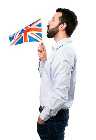 Handsome man with beard holding an United Kingdom flag