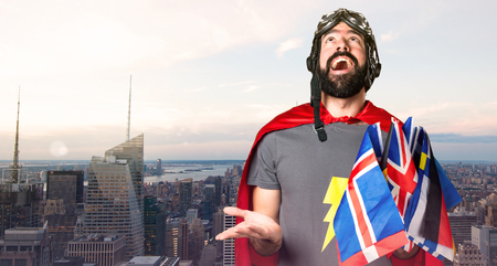 Superhero with a lot of flags pleading on unfocused city background Stock Photo