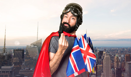 Superhero with a lot of flags making money gesture on unfocused city background