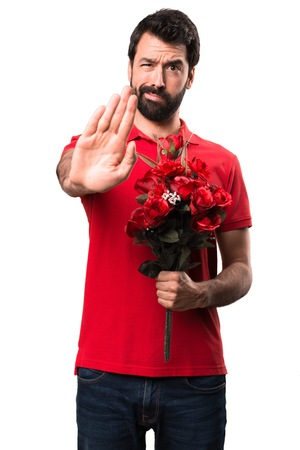 Handsome man holding flowers making stop sign over white background