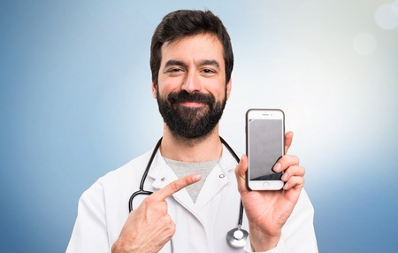 Young doctor talking to mobile on blue background