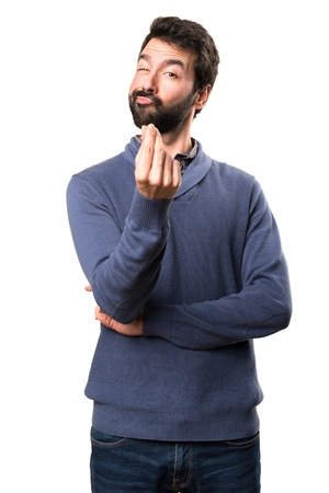Handsome brunette man with beard making money gesture on white background