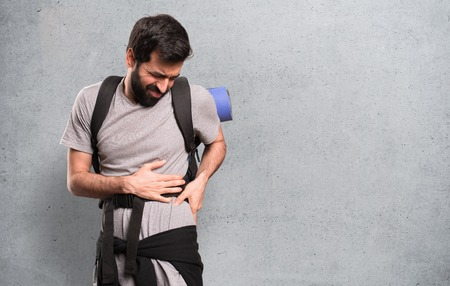Handsome backpacker with back pain on textured background Stockfoto