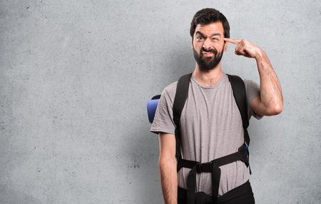 Handsome backpacker making crazy gesture on textured background