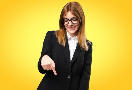 Young business woman pointing down on colorful background Banque d'images