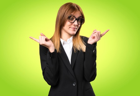 Young business woman pointing to the laterals having doubts on colorful background