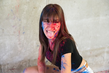 Beautiful young girl with color holi taking out her tongue Stock Photo