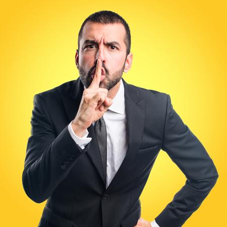 Businessman making silence gesture