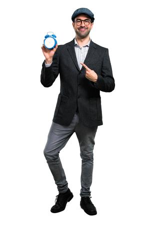 Handsome modern man with beret and glasses holding vintage clock