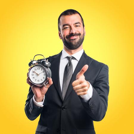 Businessman holding vintage clock