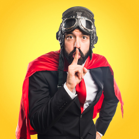 Super hero businessman making silence gesture Stock Photo