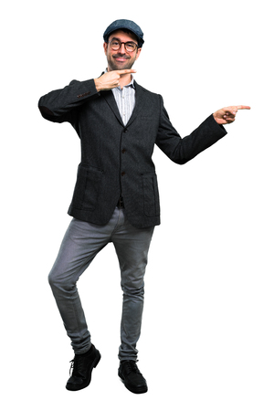 Handsome modern man with beret and glasses pointing finger to the side and presenting a product
