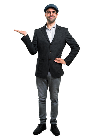 Handsome modern man with beret and glasses holding copyspace imaginary on the palm