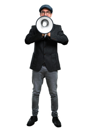 Handsome modern man with beret and glasses holding a megaphone Stock Photo