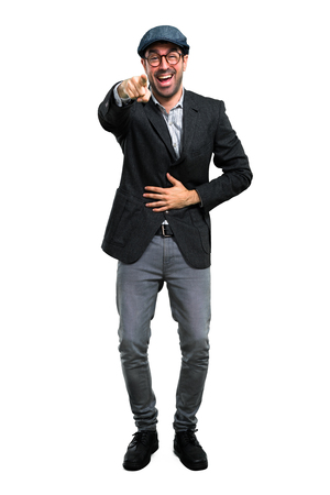 Handsome modern man with beret and glasses pointing with finger at someone and laughing a lot