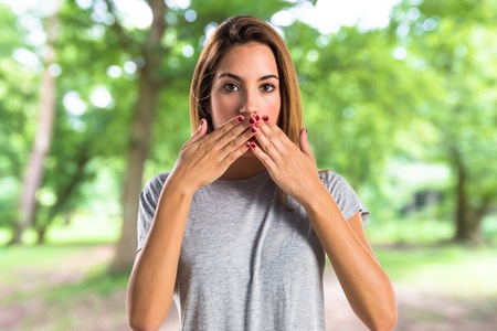 Young girl covering her mouth at the park