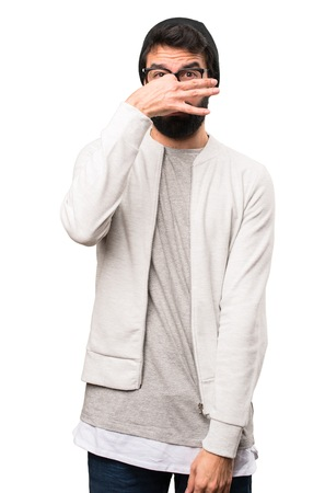 Hipster man making smelling bad gesture on white background