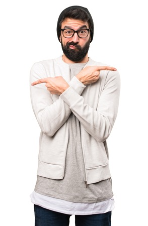Hipster man pointing to the laterals having doubts on white background