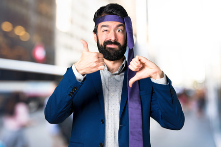 Crazy and drunk businessman making good-bad sign on unfocused background Stock Photo
