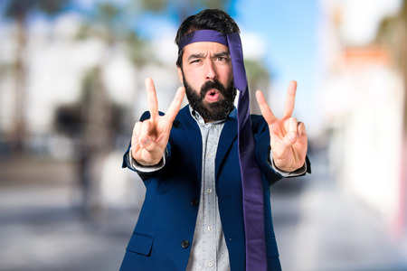 Crazy and drunk businessman making victory gesture on unfocused background
