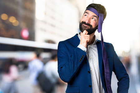 Crazy and drunk businessman thinking on unfocused background Stock Photo